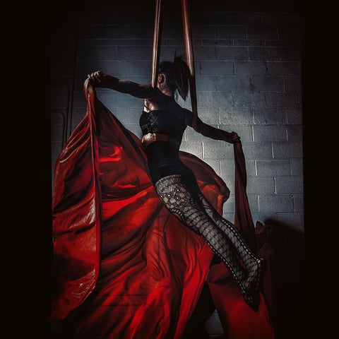 Girl holding a pose on a Red Aerial Silks