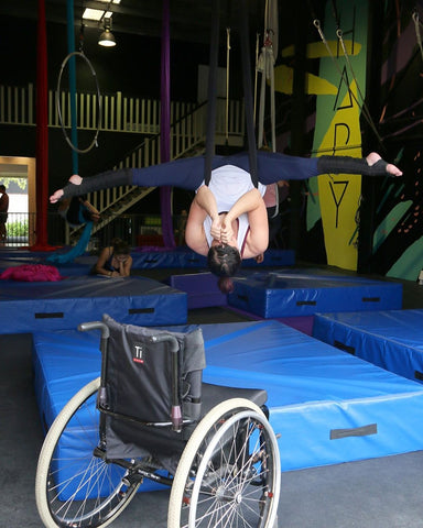Upside-down split in a black aerial hammock in front of a wheelchair