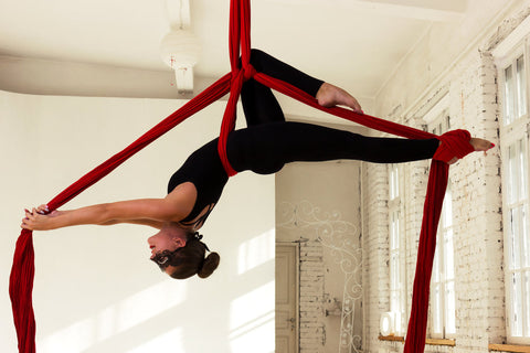 Woman Hanging on Red Aerial Silks Belay