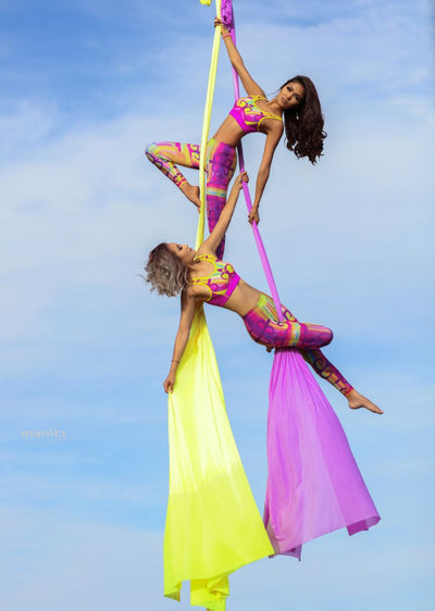 Two Women Hanging from Yellow and Lavander Aerial Silks Uplift Active