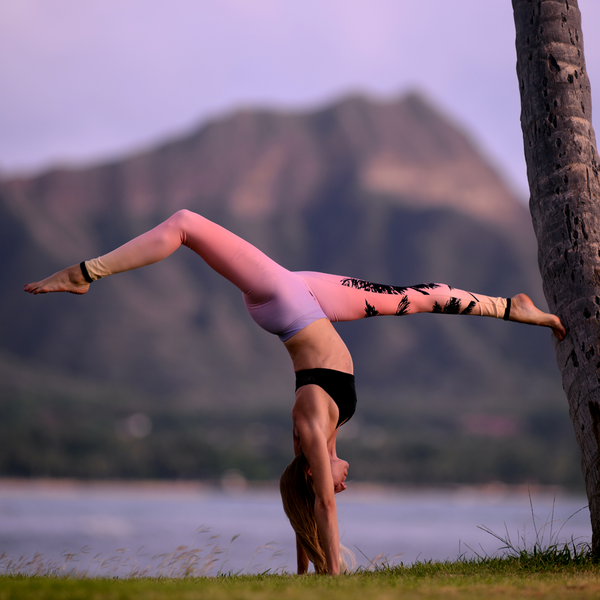 Yoga instructor Kathryn McCann practices a supported handstand while overlooking Diamond head in Oahu, Hawaii.