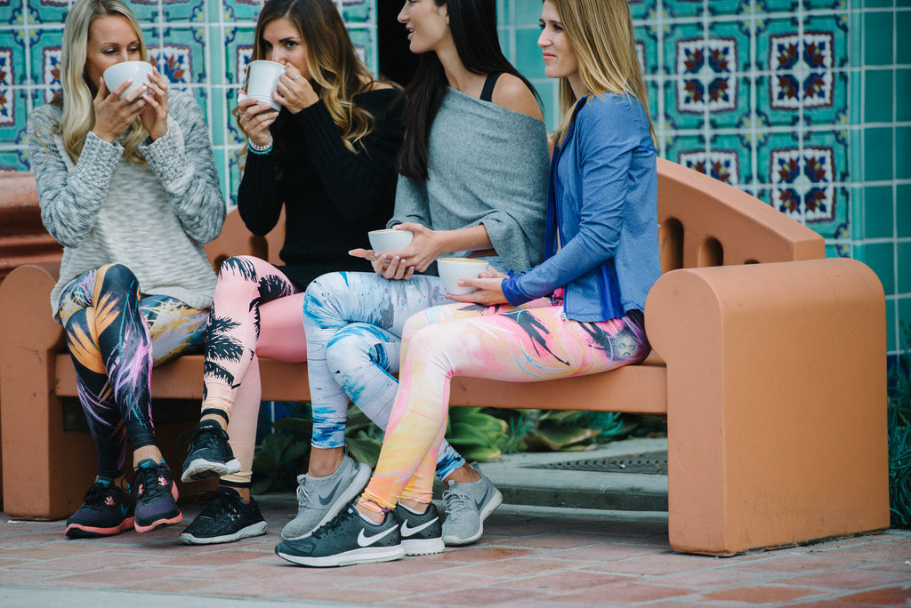 Four women sitting on a bench drinking coffee.