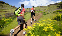 two people jogging on a hilly trail
