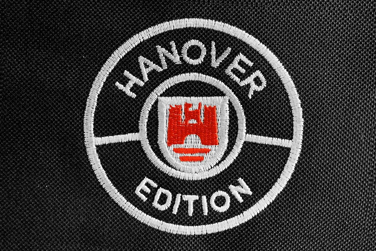 Hanover Edition logo show in white with red accent embroidered into black carpet