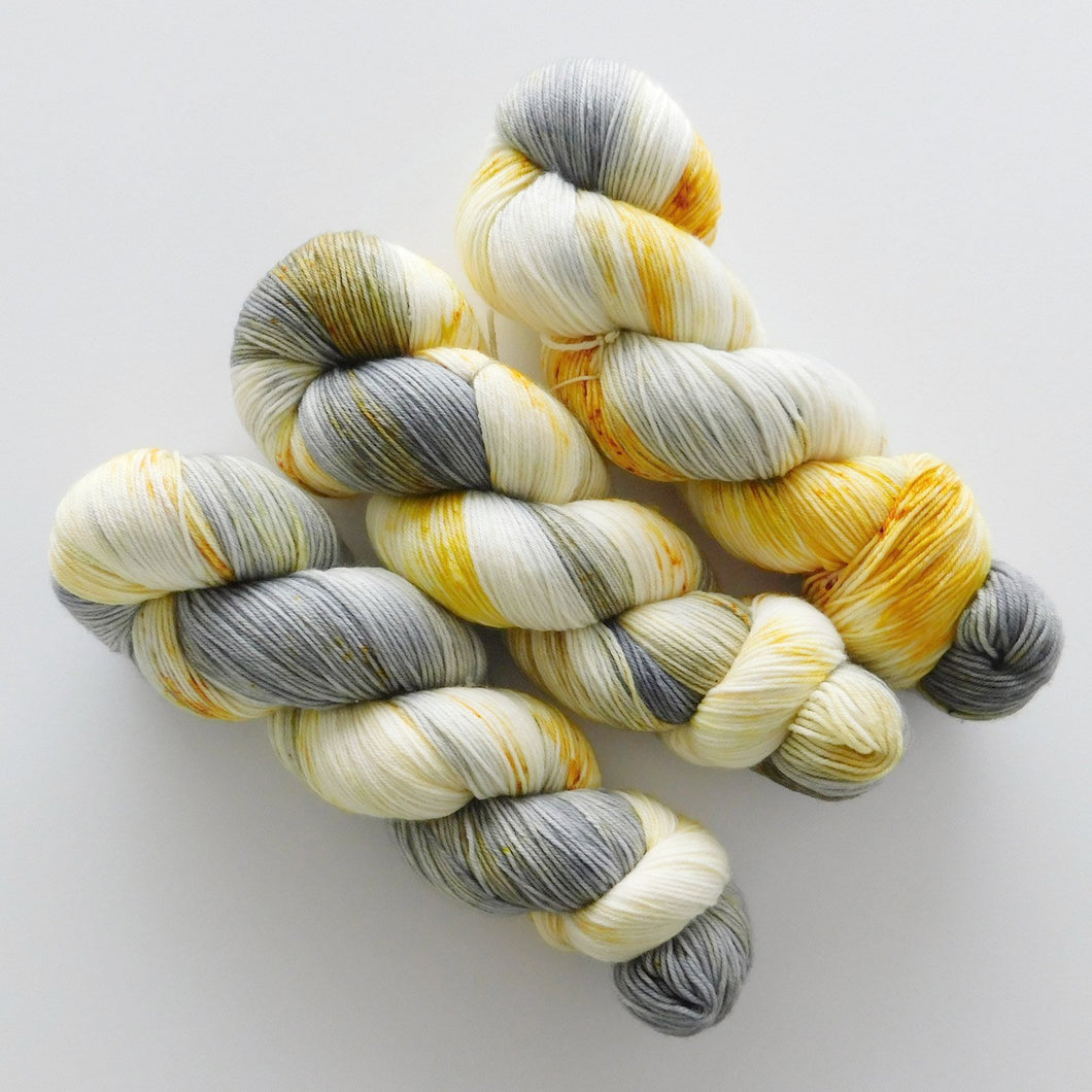 speckled hand dyed sock yarn in gray and mustard yellow -- grellow