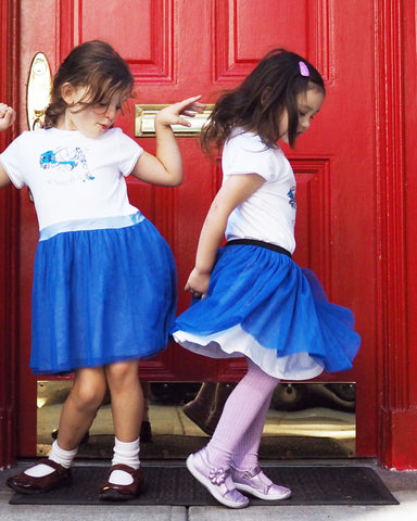 two girls wearing truck print clothing. One girl twirls her blue tulle tutu