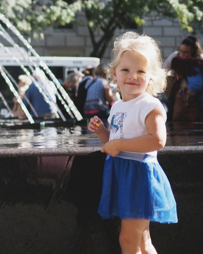 Girl wearing a blue dress with a truck print on it