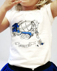 Close up of a girl wearing a white t-shirt with a cement mixer truck printed on it and adorned with gem stones