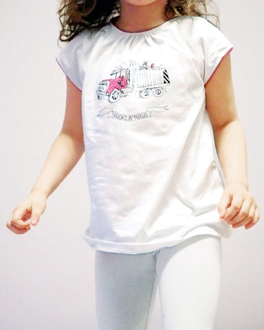 Girl wearing a white tee with a pink dump truck printed on it