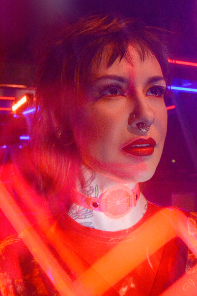 Katrina models a neon uv pink choker by Apatico and Anhedonie, a floral dress by Samantha Rei, and a red neon cross light under blue and red neon lights at night.