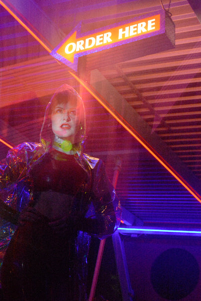 Katrina models a neon uv green choker by Apatico and Anhedonie under blue and red neon lights at night.