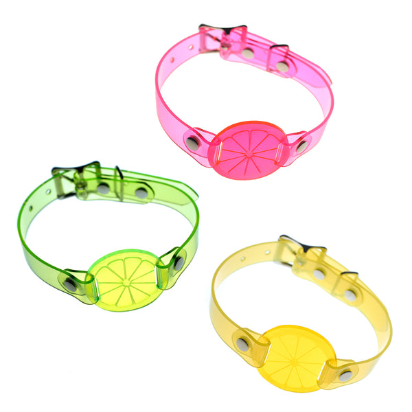 Apatico and Anhedonie choker collar necklaces in neon uv green, pink, and yellow with acrylic citrus centers.