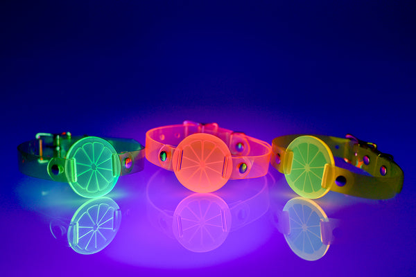 Three Apatico and Anhedonie choker collars in neon uv green, pink, and yellow with acrylic citrus centers.