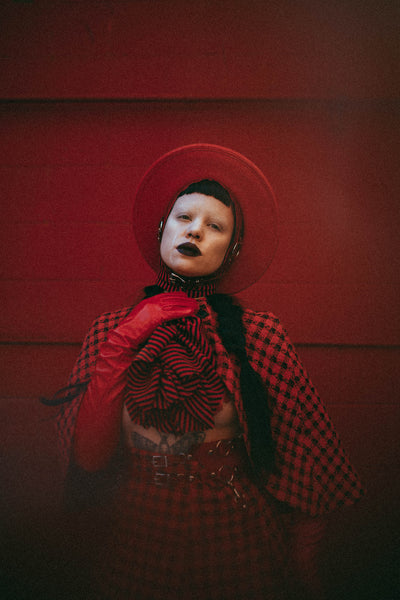 Red Apatico harness hat, red and black houndstooth fashion by Samantha Rei, photography by Emma Wondra, editorial inspired by Alexander McQueen.