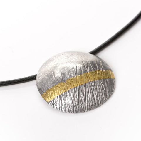 Textured disc pendant and leather necklet in oxidised silver with gold