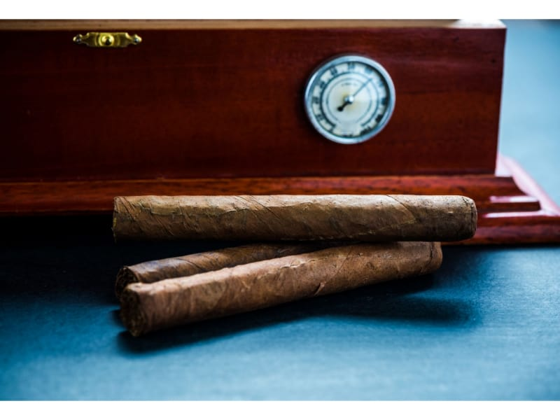 Stack of cigars beside desktop humidor with hygrometer