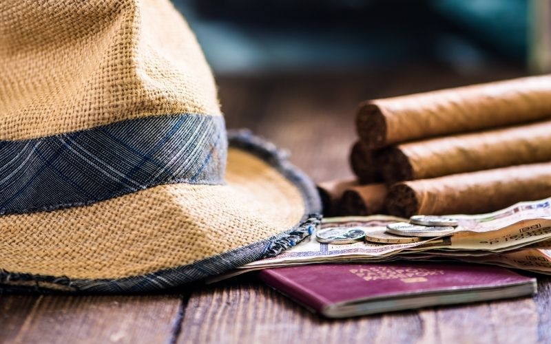 straw hat with cigars and passport