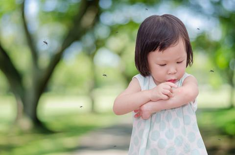 Little girl in a park examining a mosquito bite as mosquitos fly around her