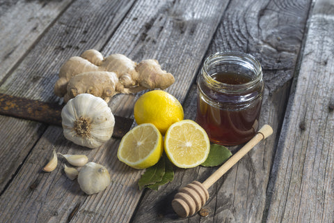 A jar of honey sits on a wooden table with lemons, garlic, and ginger