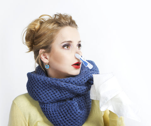 A woman in a blue scarf and yellow top looks off in the distance with a clothespin on her nose and a tissue in hand