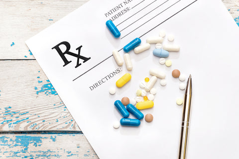 Multi-colored pills and a pen sit on a prescription pad