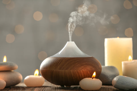 An essential oil diffuser emits steam surrounding by lit tea candles