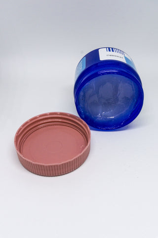 A jar of vapor rub sits on its side with a cap off