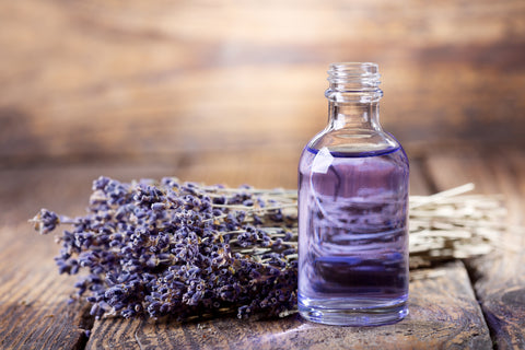 A glass bottle sits on a wooden table with a lavender plant