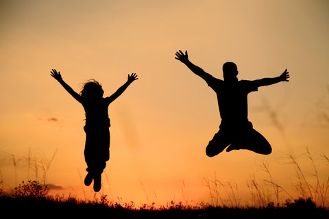 Two people jump for joy in a field at sunset