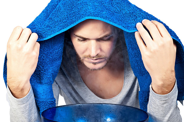 A man sits holding a blue towel over his head and blue bowl on the table in front of him with boiling water