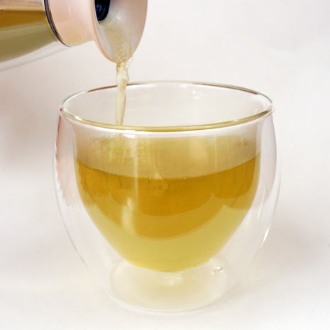 Green tea pouring into a cup