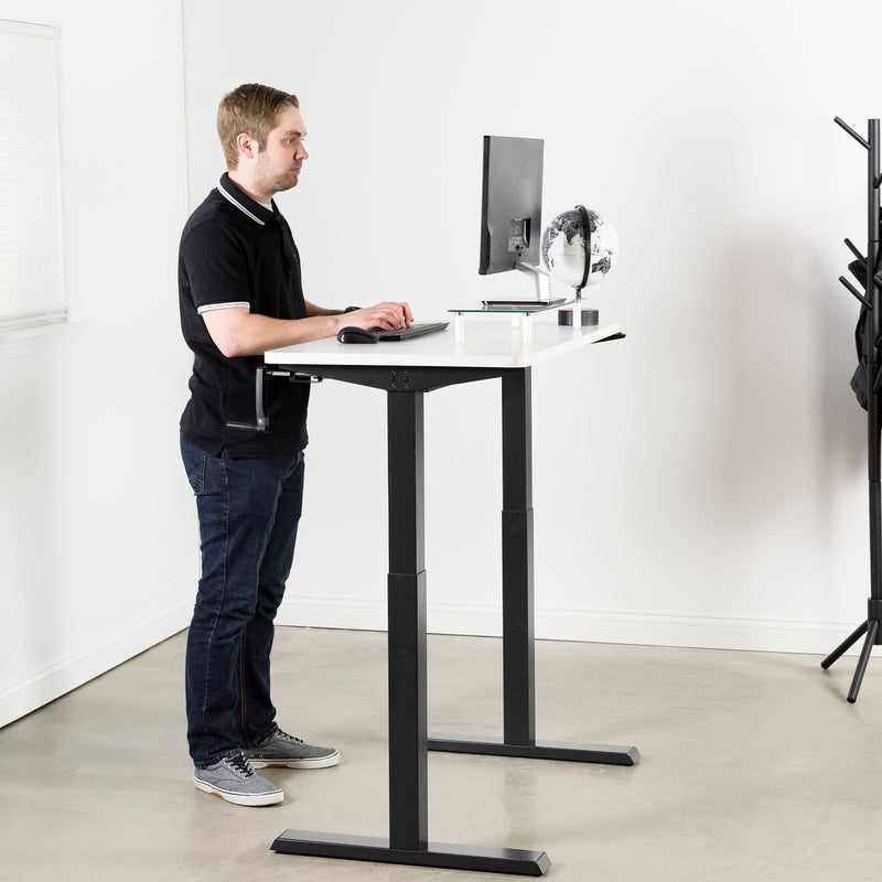 man typing on keyboard at White / Black Manual Height Adjustable Desk