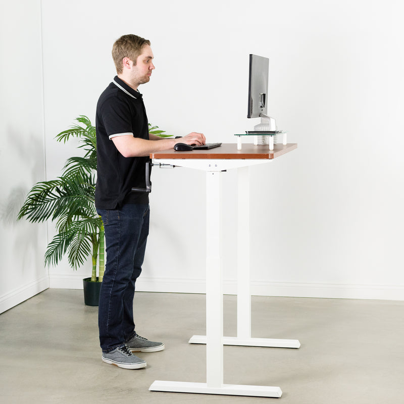 man typing at Dark Walnut / White Manual Height Adjustable Desk