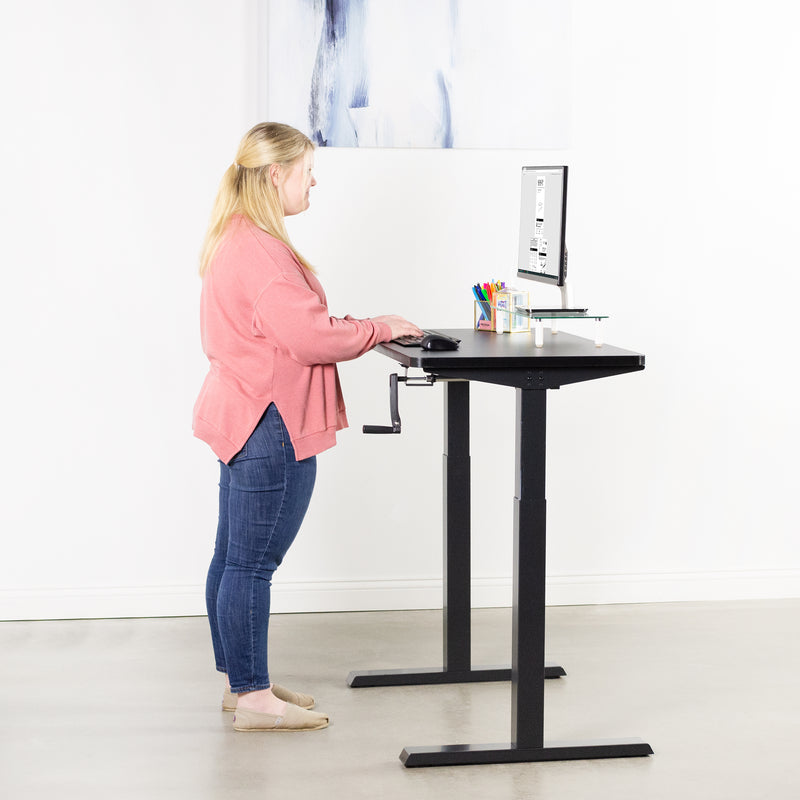 girl typing on keyboard at Black Compact Crank Height Adjustable Desk Frame with black top