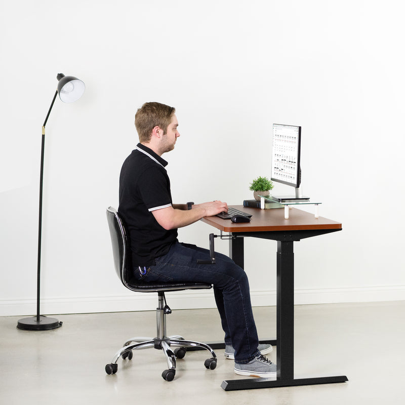 man typing on keyboard at Black Compact Crank Height Adjustable Desk Frame