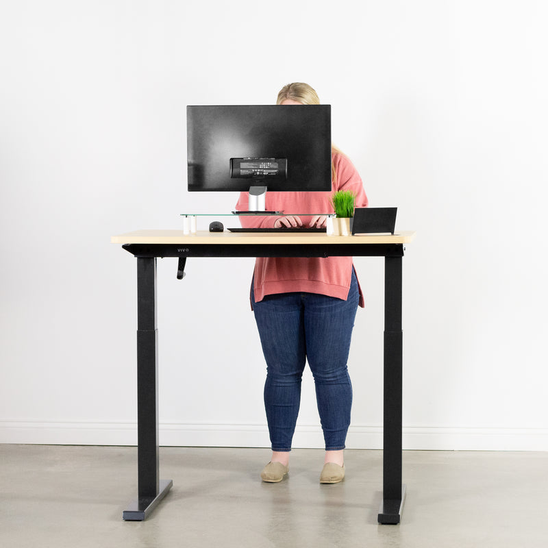 girl standing and working at black standing desk