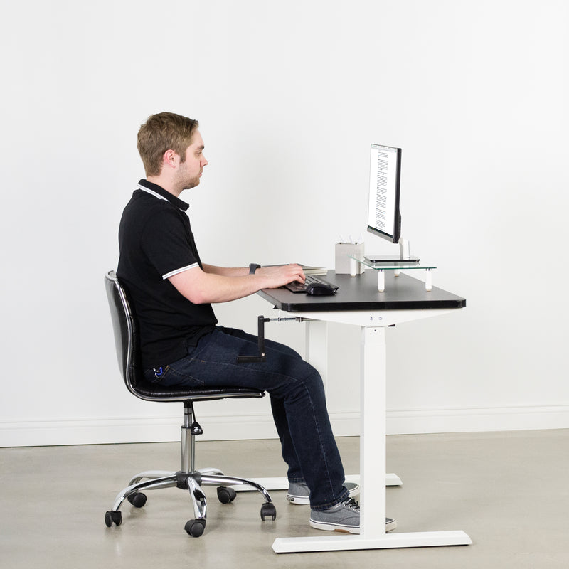 man sitting at desk with White Compact Crank Height Adjustable Desk Frame