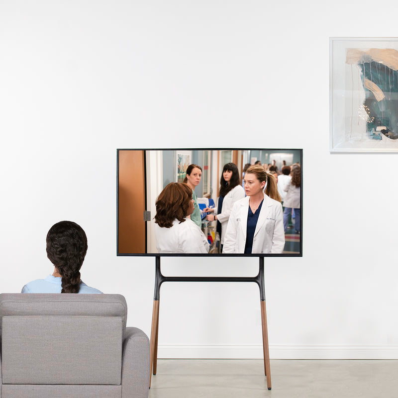 girl watching tv on Easel Studio TV Stand