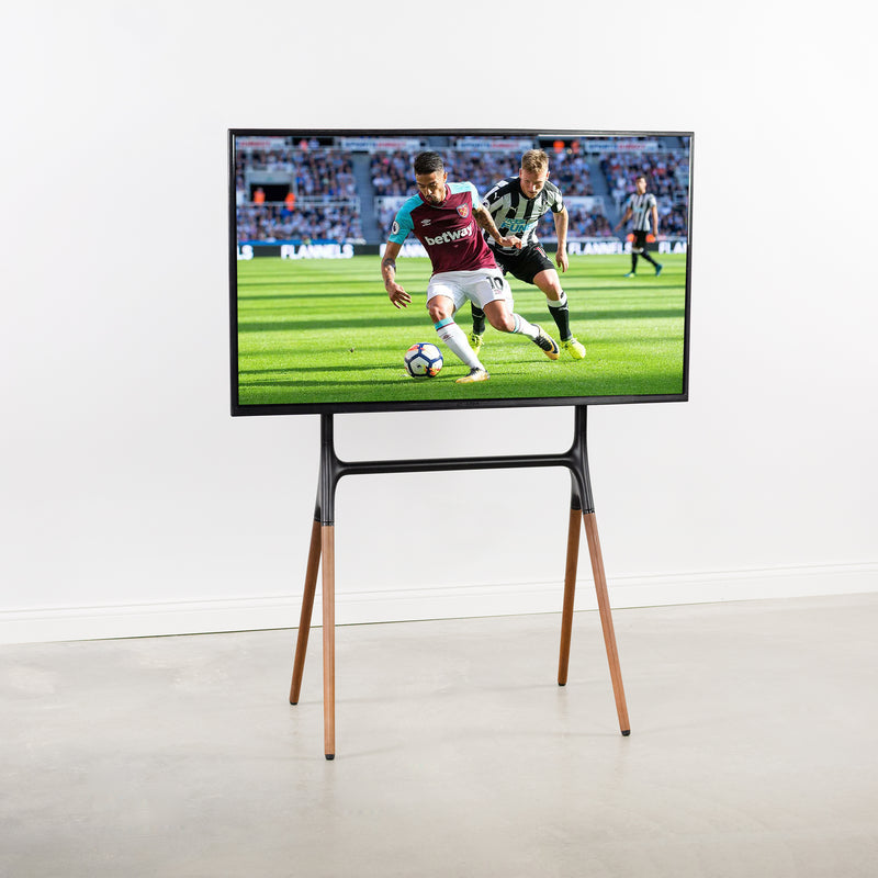 Easel Studio TV Stand with soccer playing on tv