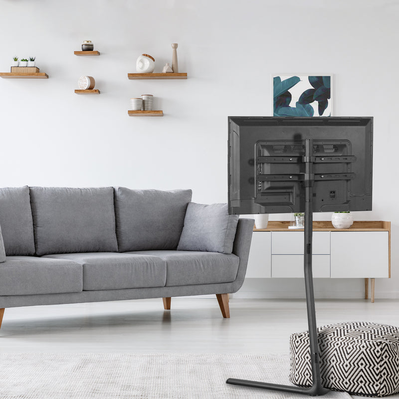 Black V-Base Studio TV Stand in living room with gray couch