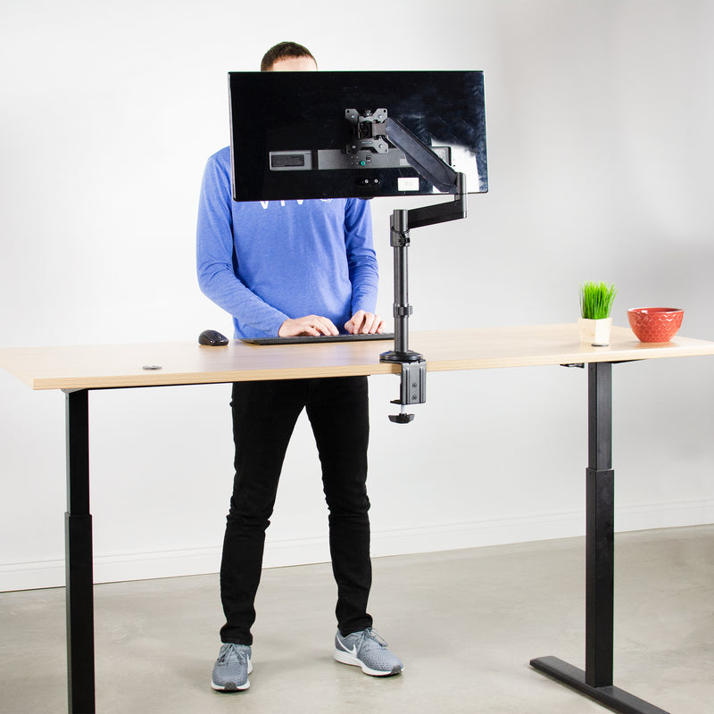 mans standing at Pneumatic Arm Single Monitor Desk Mount