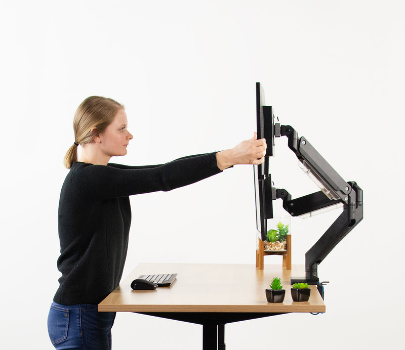 girl adjusting Pneumatic Arm Dual Monitor Desk Mount with USB