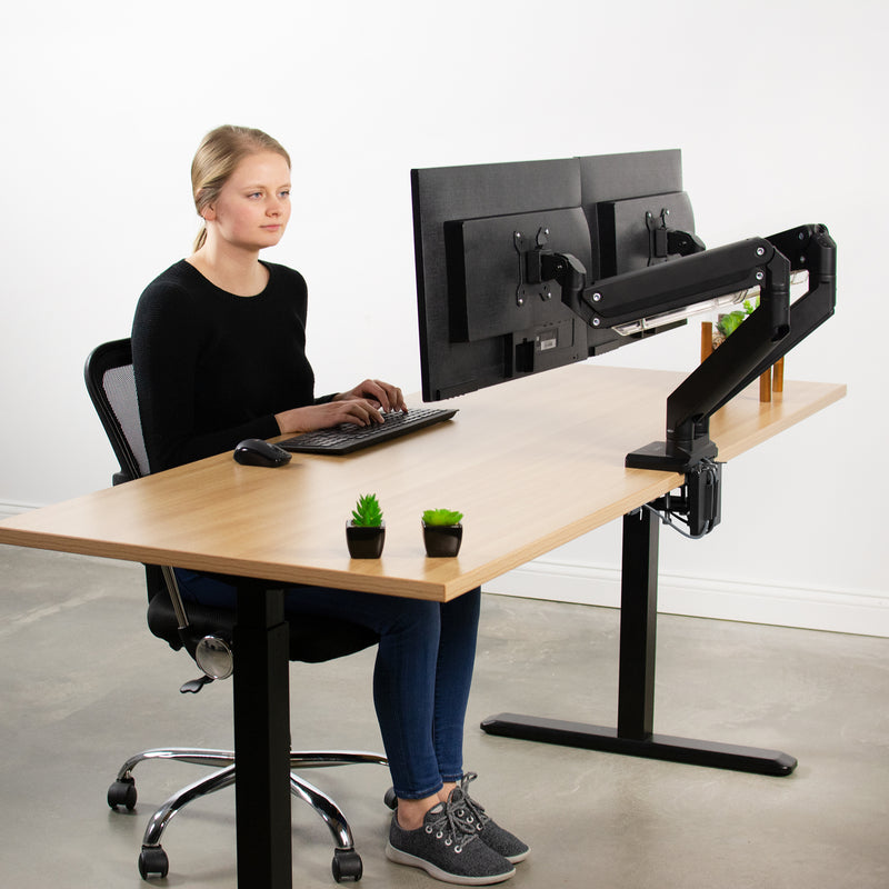 girl sitting at desk with Pneumatic Arm Dual Monitor Desk Mount with USB