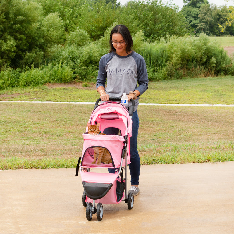 girl pushing cat in Pink Three Wheel Pet Stroller