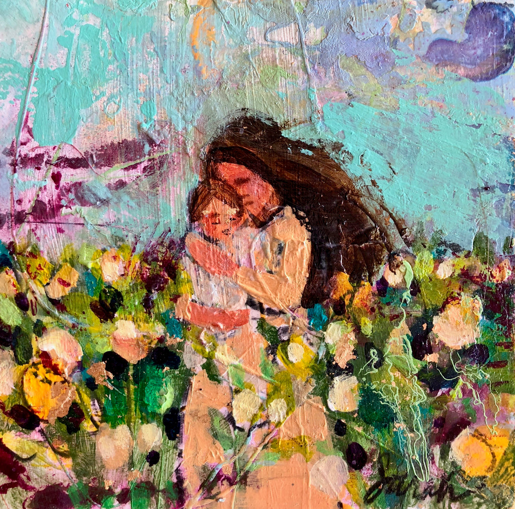 Woman in a peach dress holding her baby with long dark hair standing in a field of yellow tulips agains a turquoise sky with purples.