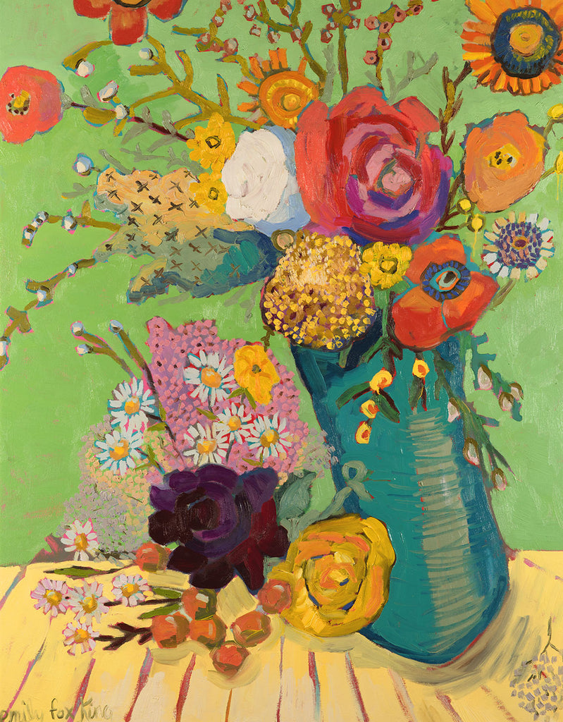 A dark turquoise vase filled with orange, pink, mustard, red and white flowers against a dark spring green wall and on a yellow cloth with red stripes.