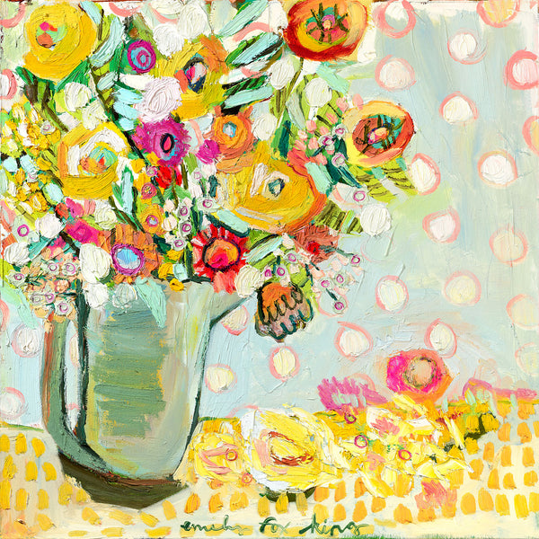A pitcher filled with bright yellow, orange and pink flowers with green and turquoise foliage against a light blue, white and pink polka dotted background on an orange and yellow squared cloth.