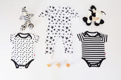 3 items of clothing all 100% cotton for a baby or young toddler. a white short sleeve bodysuit with bright black polka dots and black trim around the neck and leg openings. A white sleepsuit with bright black stars of different sizes and a black and white stripe short sleeve bodysuit with black trim around the neck and leg openings.