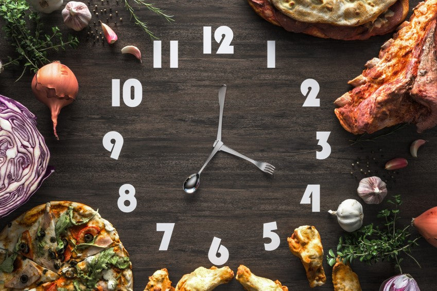 Clock on a wood table with food around it.