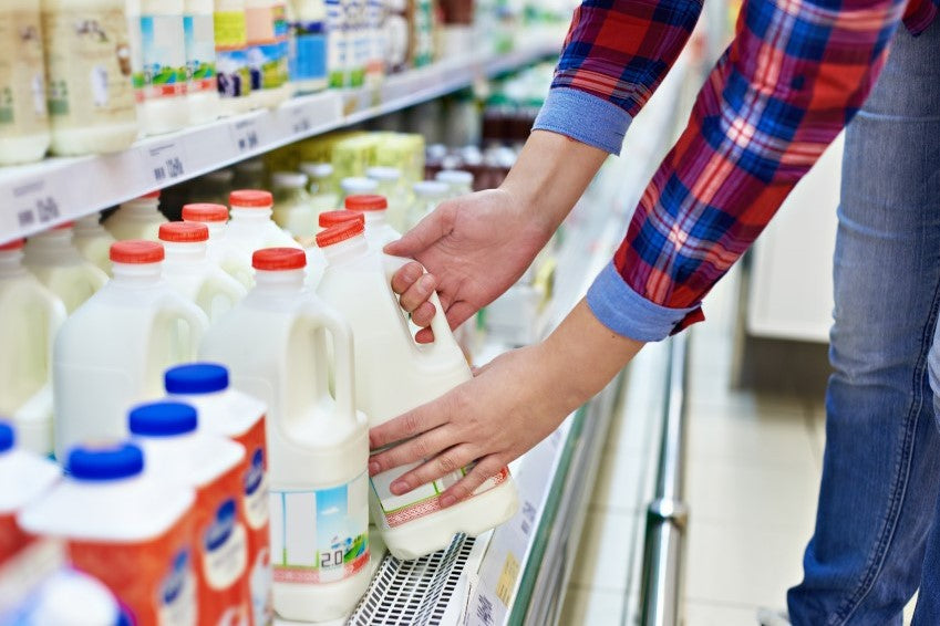 Picking a half gallon of milk at the grocery store for protein.